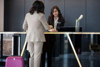 Recepcionista de hotel tendiendo cliente